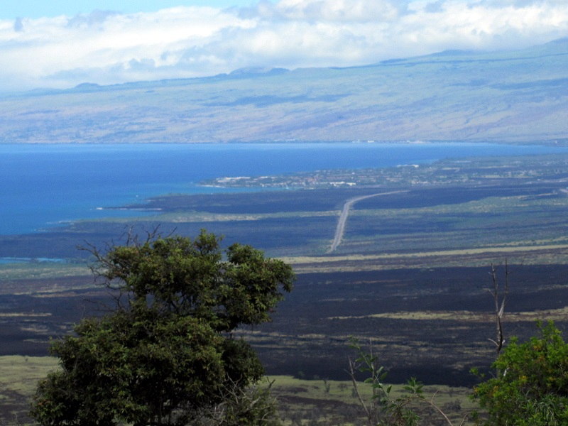 """We often talk about Ironman athletes cycling and running over """"lava fields."""" This shot from high up on the Mamalahoa Highway provides a stark illustration of these """"fields."""" That's the Queen K Highway cutting through lava laid down in 1801 by the now-dormant Hualalai that looms above Kailua-Kona. (Not for nothing, but """"dormant"""" does not mean """"extinct."""" Hualalai is considered active, and is expected to erupt again within the next 100 years.)"""